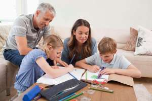 Parents helping their children to do their homework in their living room